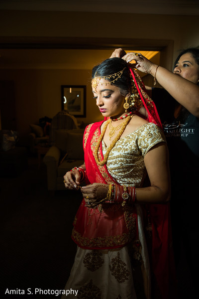 Maharani being assisted with her bridal accessories