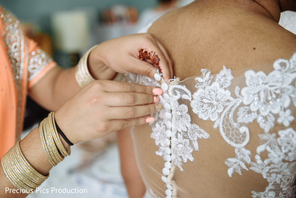 Indian bride getting her white dress on.