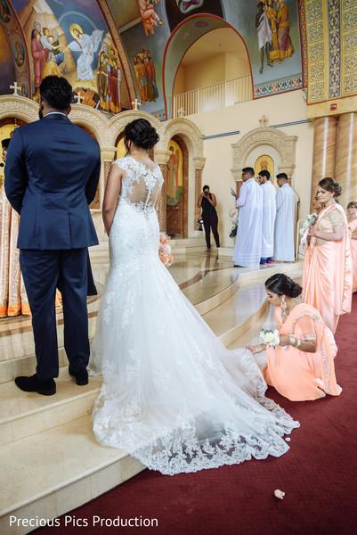 Indian bridesmaid helping Indian bride.