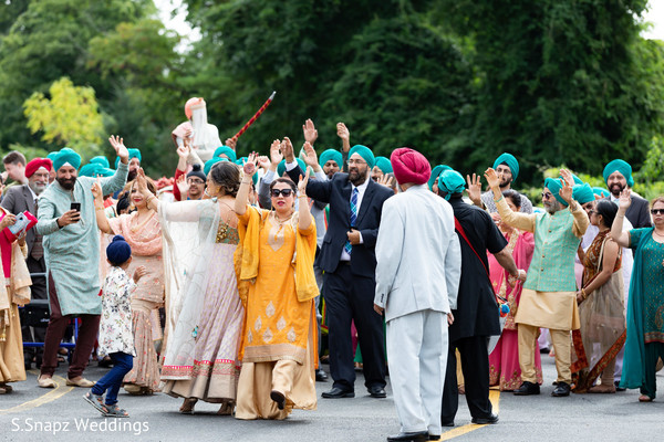 Indian groom and joyful guests during the baraat