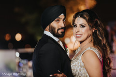 Lovely Indian bride and groom celebrating at reception party.