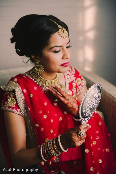Gorgeous indian bride looking in the mirror.