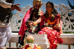 Indian bride and groom pouring into sacred fire