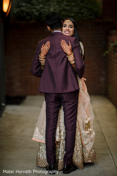 Indian bride and groom hugging each other.