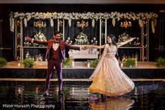 Gleeful indian bride and groom's wedding reception dance.