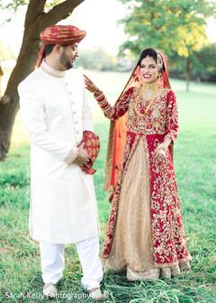 Ravishing Indian bride  and groom posing out doors.