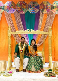 Indian couple posing for pictures under the mandap