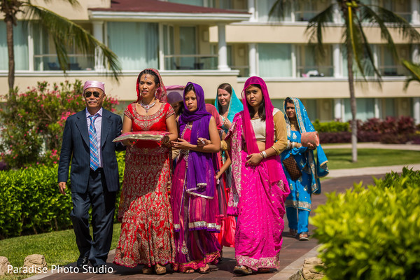 Indian bride walking  in with father and bridesmaids.