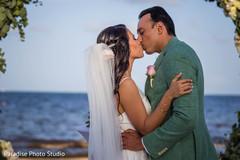 Adorable Indian bride being kissed by groom.