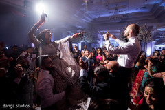 Indian bride being lifted by guests during the dance