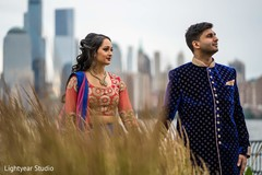 Indian bride holding the raja's hand during the photo shoot