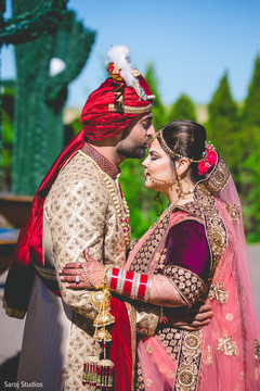 Lovely Indian  groom kissing bride photo session.