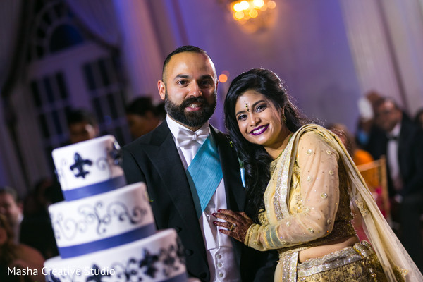 Adorable indian newlyweds next to their cake