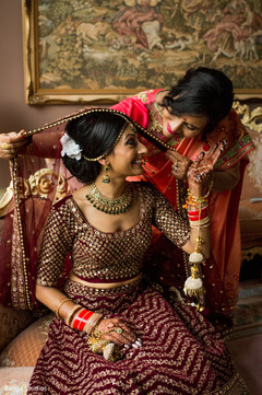 Indian bride being assisted by her mother with the accessories