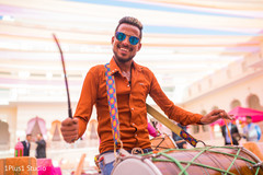 Capture of cheerful guest playing the dhol