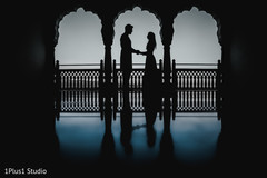 Indian bride and groom holding hands for pictures