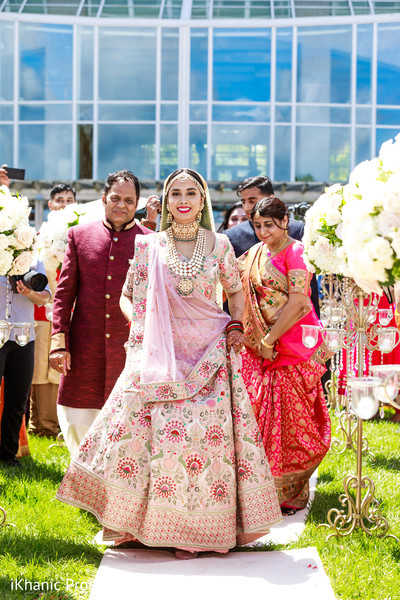 Glamorous Indian bride walking  in to ceremony.