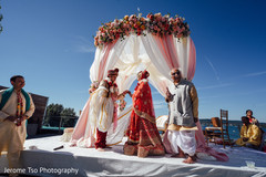Indian bride and groom under the beautiful mandap