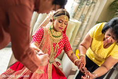 Indian bride getting help while getting ready