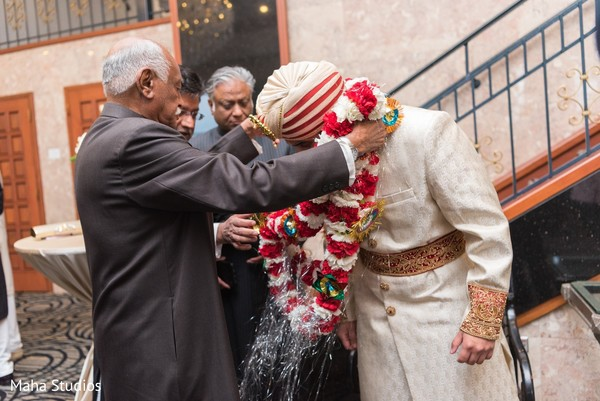 Indian groom receiving the garland by special guests