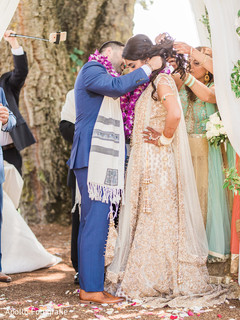 Indian groom placing a mangamalai to bride during wedding ceremony.
