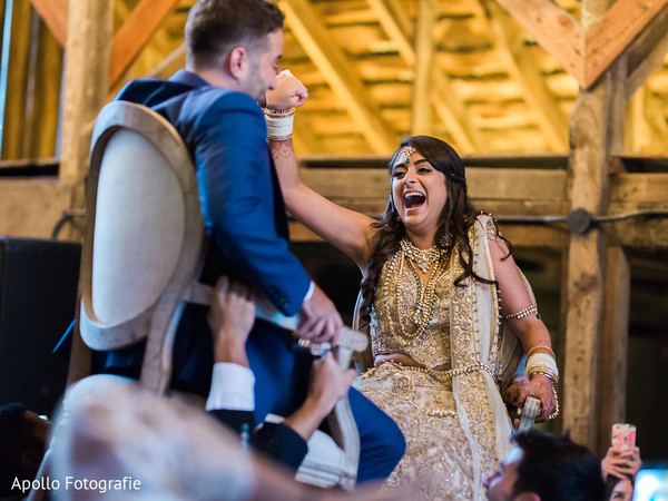 Joyful Indian newlyweds are lifted by guests