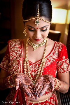 Cute Indian bride admiring her mehndi art.