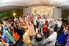 Indian bride and groom with wedding guests rocking the dance floor.