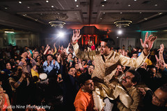 Indian groom being lifted by groomsmen at sangeet.
