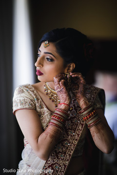 Dazzling Indian bride putting her earrings on.