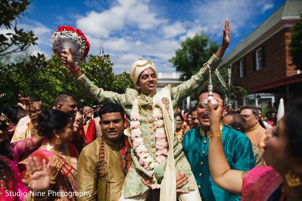 Indian groom with groomsmen during baraat