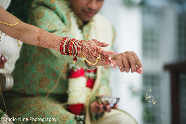 Indian bride and groom throwing the rice to sacred fire.