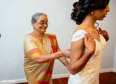 Indian bride being helped by special guest before the ceremony
