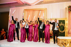 Indian bridesmaids and groomsmen cheering during the reception