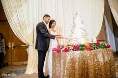 Indian newlyweds cutting the wedding cake