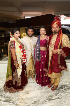 Glamorous Indian bride and groom with guests portrait.