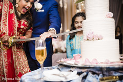 Indian bride and groom using the kirpan to cut the cake