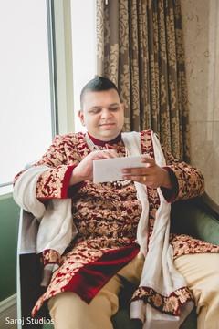 Indian groom reading maharani's card
