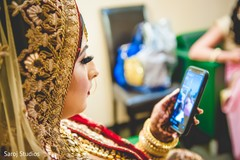 Indian bride checking her phone as she gets ready