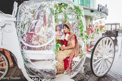 Capture of Indian bride riding the wedding carriage