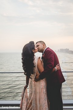 Indian bride and groom kissing by the sea