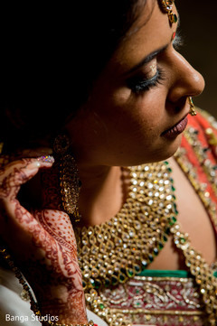 Indian bride putting earrings on.
