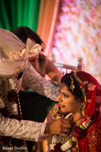 Indian groom putting a necklace to bride during the ceremony ritual.