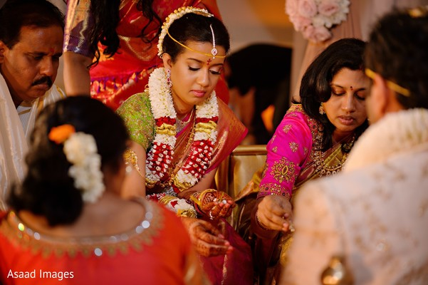 Adorable indian bride making offerings to sacred fire.
