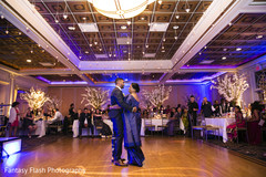 Indian groom dancing with parent capture.