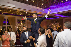 Indian groom being lifted up during reception.