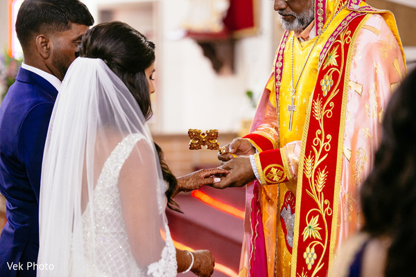 Indian bride being blessed by priest.