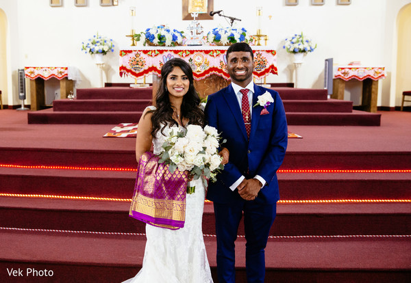 Indian couple posing next to each other at wedding ceremony.