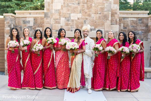 Beautiful bridesmaids pose with the joyful Indian couple