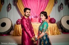 indian couple posing at pre-wedding celebration sangeet.